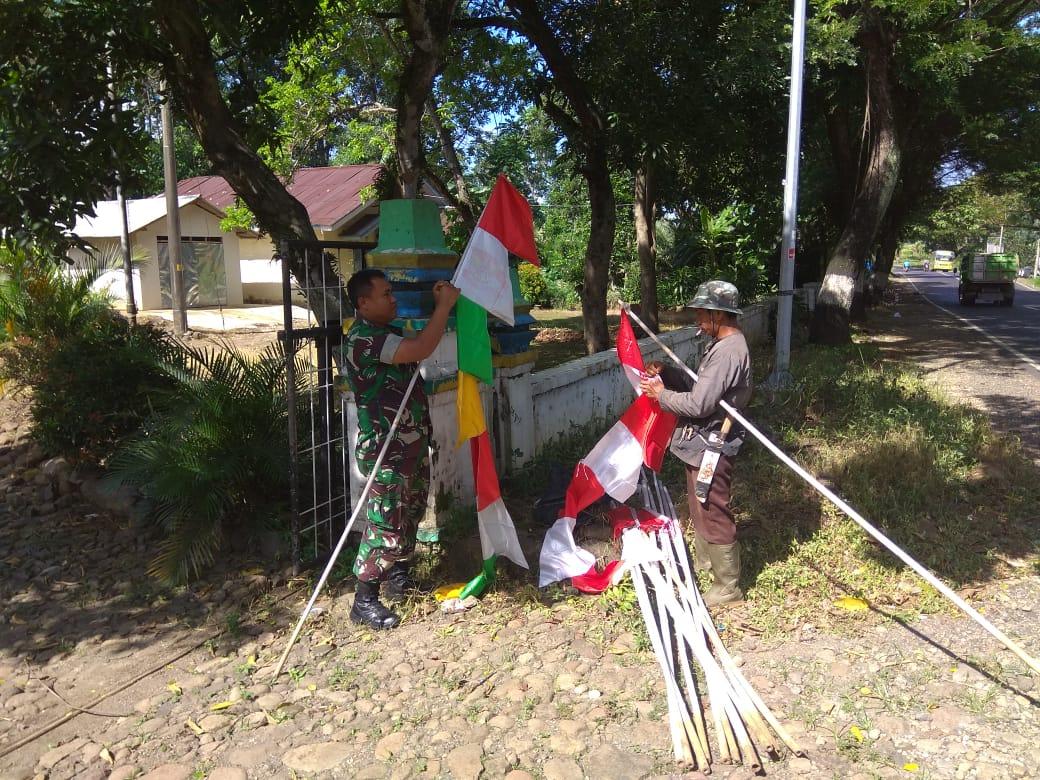 BABINSA PASANG BENDERA UMBUL-UMBUL DIBANTU WARGA